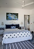 Striped and polka dot patterns on bed linen and rug in rustic bedroom with ceiling fan