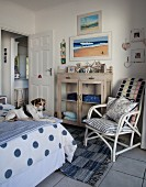 Dog on bed, white bamboo chair with cushions and cabinet with glass doors in rustic-maritime bedroom