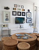 View across rattan coffee table with matching stools in various sizes to flatscreen TV and gallery of pictures on wall above white sideboard