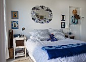 Double bed with white and blue polka-dot bed linen and shabby chic bedside table in bedroom