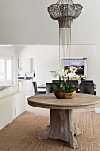 Bowl of orchids on round, solid-wood table below pendant lamp with metal beaded lampshade in open-plan elegant interior