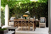 Long dining table and bentwood chairs flanked by wicker chairs on paved, summery terrace