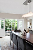 Dining table, dark brown upholstered chairs, designer pendant lamp and open French windows