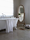 Antique-style cheval mirror and vintage, free-standing bathtub below window