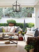 Sofas with wicker frames and scatter cushions around simple wooden coffee table on terrace with lantern hanging from ceiling