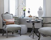 Grey, antique-style armchairs and tea set on matching side table below window