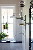 Sconce lamp with glass lampshade next to white-tiled shower area behind glass screen