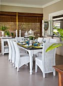 White wicker chairs around set table in loggia in front of closed bamboo blinds