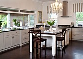 Dark wooden chairs at dining table adjoining counter in kitchen with white, country-house-style cabinets