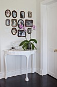 Orchid on white-painted console table below gallery of framed photos on wall