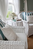 White-painted wicker armchairs with cushions and vase of white flowers on round side table in front of window