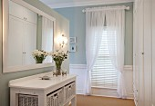 Console table with white wicker boxes below mirror on wall; draped curtains and louvre blinds on window in background
