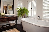 Free-standing bathtub below window, antique washstand with countertop basin below framed mirror and fern on plant stand in corner