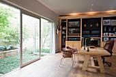 Massiver Holzschreibtisch mit Bürostuhl vor Bücherwand vor Terrassentür