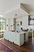 White, open-plan, country-house kitchen with oak floor and island counter