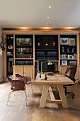 Massiver Holzschreibtisch mit Lederbürostuhl vor beleuchteter Bücherwand