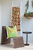 Kissen auf gebogenem Rattanstuhl neben Beistelltischchen, an Wand weiss lackierte Leiter mit buntem Ethnomuster dekoriert