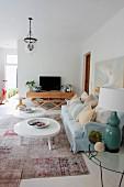 Couchtische mit weisser, amorpher Platte vor hellblauem Polstersofa in eklektischem, grossräumigem Wohnzimmer