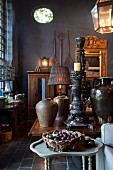 Freshly picked plums in basket on side table in front of antique, ethnic collectors' items on table in converted barn with black-painted walls