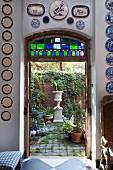 Blick durch offene Tür in den begrünten Hinterhof auf antik griechisches Pflanzengefäss und Ziegelmauer