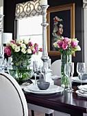 Festlich gedeckter Tisch mit Blumensträussen und Silber Kerzenhalter, im Hintergrund Gemälde an schwarzer Wand