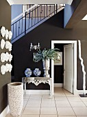 Hallway with dark walls, theatrical masks on wall and guest bathroom below staircase
