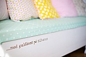 Bench with painted motto and pastel, patterned scatter cushions on polka-dot seat cushion