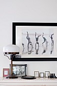 Framed photo on wall above Art Deco, vintage table lamp