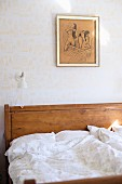Bed with wooden headboard and white bed linen against wall with patterned wallpaper
