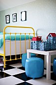 Yellow, vintage, metal-framed bed and pale blue pouffes around toy castle on small table on chequered floor