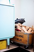 Wooden toys in upcycled wooden box on castors next to pastel blue retro dresser
