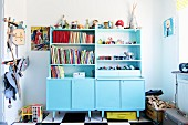 Dressers painted pale blue in child's bedroom with toy box and knights' armour