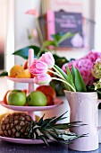 Tulpen in rosa Keramikkrug neben Etagere mit Früchten
