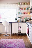 Pastel, retro crockery on open-fronted shelving, white bar stool at kitchen counter and floral rug on parquet floor