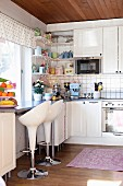 White bar stools at counter below window in country-house, retro kitchen