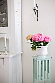 Pink hydrangea in white pot on pastel green, fifties-style flower stand