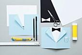 Bastelutensilien für die Anfertigung einer eleganten Einladungskarte zum Herrenabend
