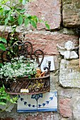 Rustic brick wall with cherub ornament and potted flowering plant in metal holder