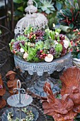 Decorative wreath of succulents with sempervivums on metal stand behind rust bird figurines