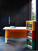 Books in stacked, colourful wooden modules in front of desk with orange plastic panel