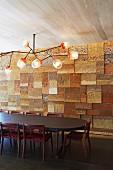 Massgefertigte Deckenleuchte mit Glasschirmen über Esstisch, gegenüber Wand mit reliefartig verlegten Steinfliesen