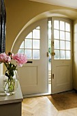 Arched front door with lattice windows in foyer with bouquet on console shelf in foreground