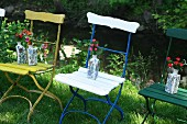 Ceramic vases of flowers on vintage garden chairs with colourful metal frames