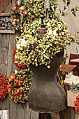 Tailors' dummy with wreath of hops on autumn market