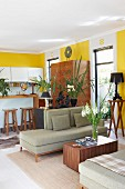 Cubic wooden coffee table between retro chaise longue and kitchen area in open-plan interior with yellow-painted walls