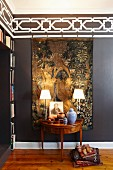 Table lamps on Biedermeier-style console table in front of antique Flemish tapestry on dark brown wall with stencilled black and white frieze