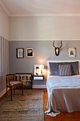 Rustic bedroom with hunting trophy above bed on wall painted pale grey