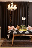 Orchids on yellow tray on retro wooden table below chandelier with beaded ornaments in front of brown curtain
