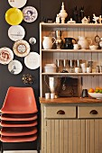 Stack of orange shell chairs below decorative plates on dark brown wall next to country-style dresser