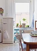 Vintage dining set opposite fifties fridge in retro kitchen in period building